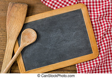Chalkboard with wooden spoons on a red checkered tablecloth