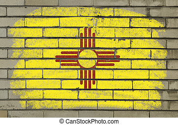 Chalky and grunge american state of new mexico flag painted with color chalk on brick wall