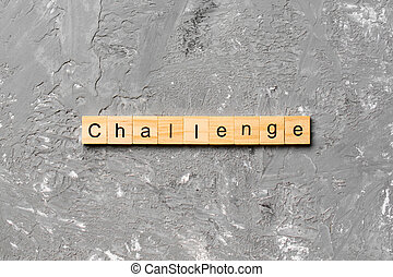 CHALLENGE word written on wood block. CHALLENGE text on cement table for your desing, concept