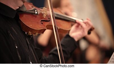 Chamber orchestra. A person passionaly plays violin. Hands...
