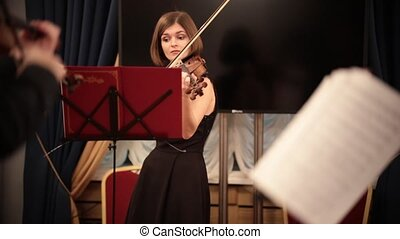 Chamber orchestra. A young beautiful woman playing violin...