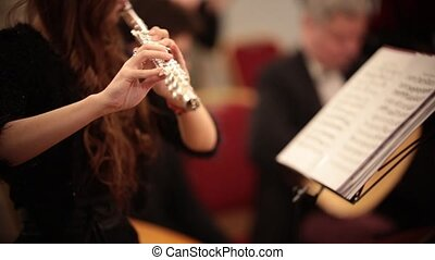 Chamber orchestra. A young woman playing flute. Close up