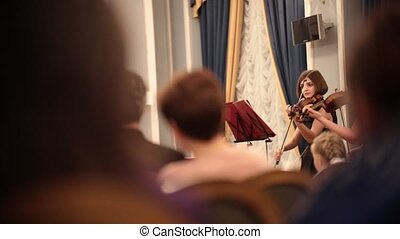Chamber orchestra. A young woman playing violin during a...