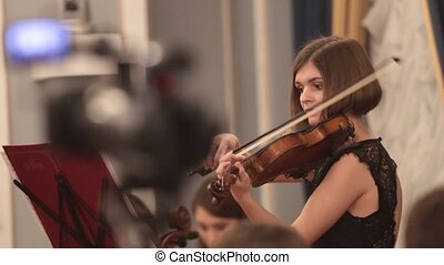 Chamber orchestra. A young woman playing violin. Finishing...