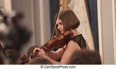 Chamber orchestra. A young woman playing violin. Mid shot