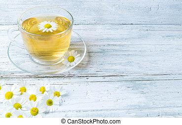Chamomile tea on wooden background
