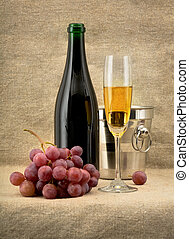 Champagine bottle, grape and goblet on canvas background