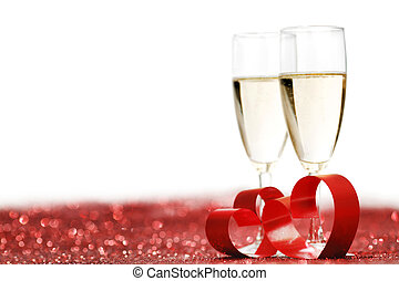 Champagne and valentines day decoration on red glitter...