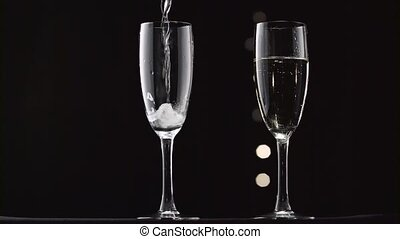 Champagne being poured into two transparent glass. Bokeh...