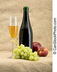 Champagne bottle, goblet, grapes, apple and peach