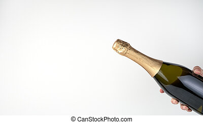 Champagne bottle in hand on a light background.