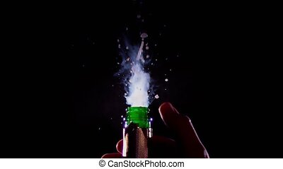 Champagne bottle is opened and sprinkled. Slow motion, black...
