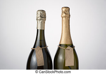 Champagne bottles with hand labels on a light background.