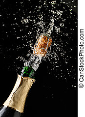 Champagne cork popping and splashing on black background....