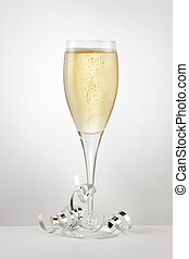 Champagne flute filled with champagne, surrounded by silver streamers