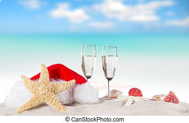 Champagne flutes with santa cap on sunny beach, celebration theme.