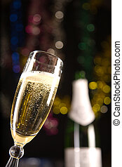 Champagne glass, blurred bottle on background