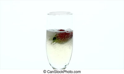 Champagne Glass Closeup - two strawberries are dropped into ...