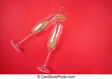 Champagne glass with colorful sugar sprinkles on red background.