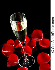 champagne glass with petals of rose isolated on black background
