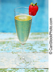 Champagne glass with strawberry on turquiose background...