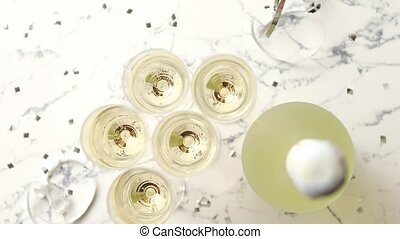 Champagne glasses and bottle placed on white marble...