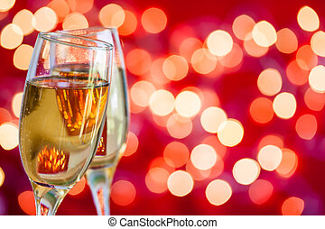 Champagne glasses on light bokeh red background