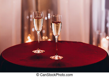 champagne glasses on red table at evening wedding ceremony reception, with lights on background. space for text. christmas new year feast, luxury life celebration