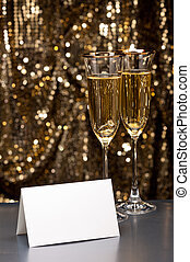 Champagne glasses with submerged ring in front of gold glitter background