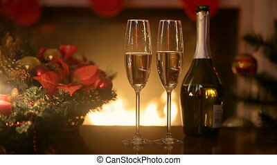 Champagne in two glasses on table in front of burning fireplace at living room decorated for Christmas