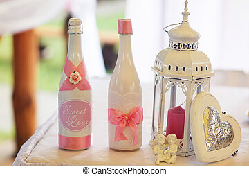 Champagne in white bottles stand behind a white lantern with red candle