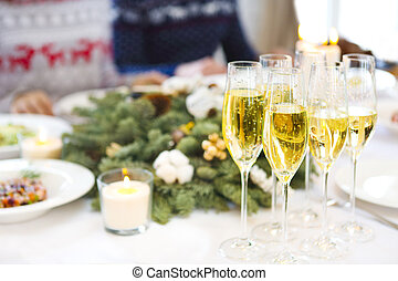 Champagne into a glasses standing on the Christmas table