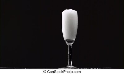 Champagne is poured into the misted glass on a thin stalk....