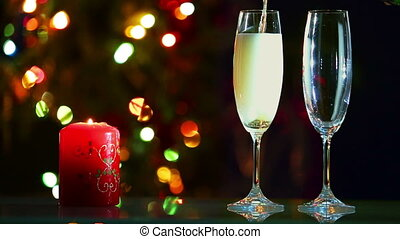 champagne is pouring into glasses and candle - romantic evening