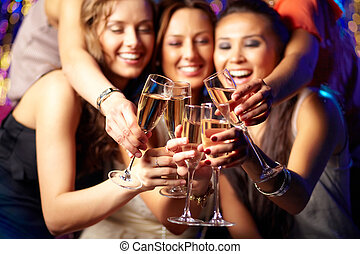Champagne party - Cheerful girls clinking glasses of...