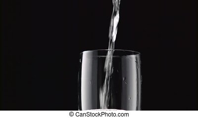 Champagne poured into glass. Black background. Close up -...