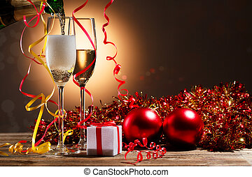 Champagne pouring from bottle into glasses and Christmas...