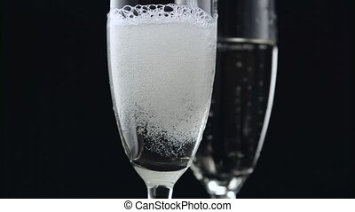 Champagne pouring from bottle into two glasses on black background. Close up
