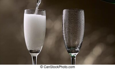 Champagne pouring in two glasses of steamy green bottle....