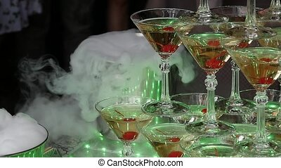 Champagne pyramid for parties with cherries and dry ice in the form of a slide. Festive table setting for the big Banquet. Slow motion