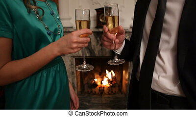 Champagne - Smart couple clinking flutes with champagne at...