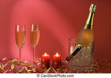 champagne with two glasses and candles on red background