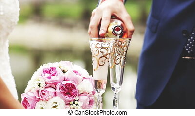 Champagne - Groom pours champagne glasses clink glasses and...