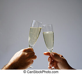 Champagne toast in sun - two hands with champagne flutes...