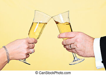 Photo of a man and womans hands toasting with a glass of champagne