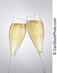 """Champagne toast - Two filled champagne flutes \""""clink\"""" to a..."""