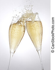 Two filled champagne flutes touch in a spill over toast