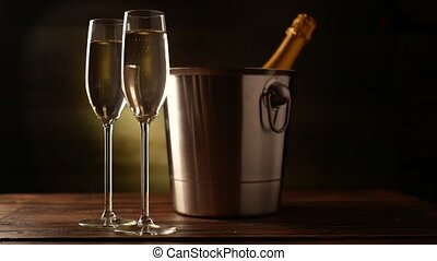 Champagne. Two Flutes with bottle of champagne in an ice bucket at background.