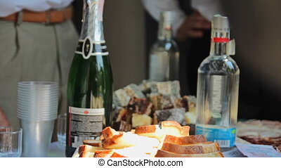 Champagne, vodka, sliced bread and a snack on the table....