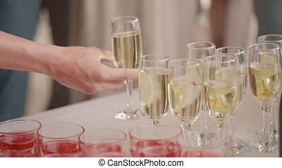 Champagne with glasses is on table for people. Hand takes one glass of alcohol during festive occasion. Guest is treated to strong drink at party against backdrop of crowd. Restaurant crystal drinks at bar in nightlife. Luxurious taste and pleasure at holiday.
